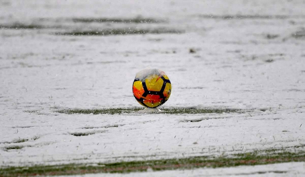 Pallone di calcio che rotola nelle pozzanghere